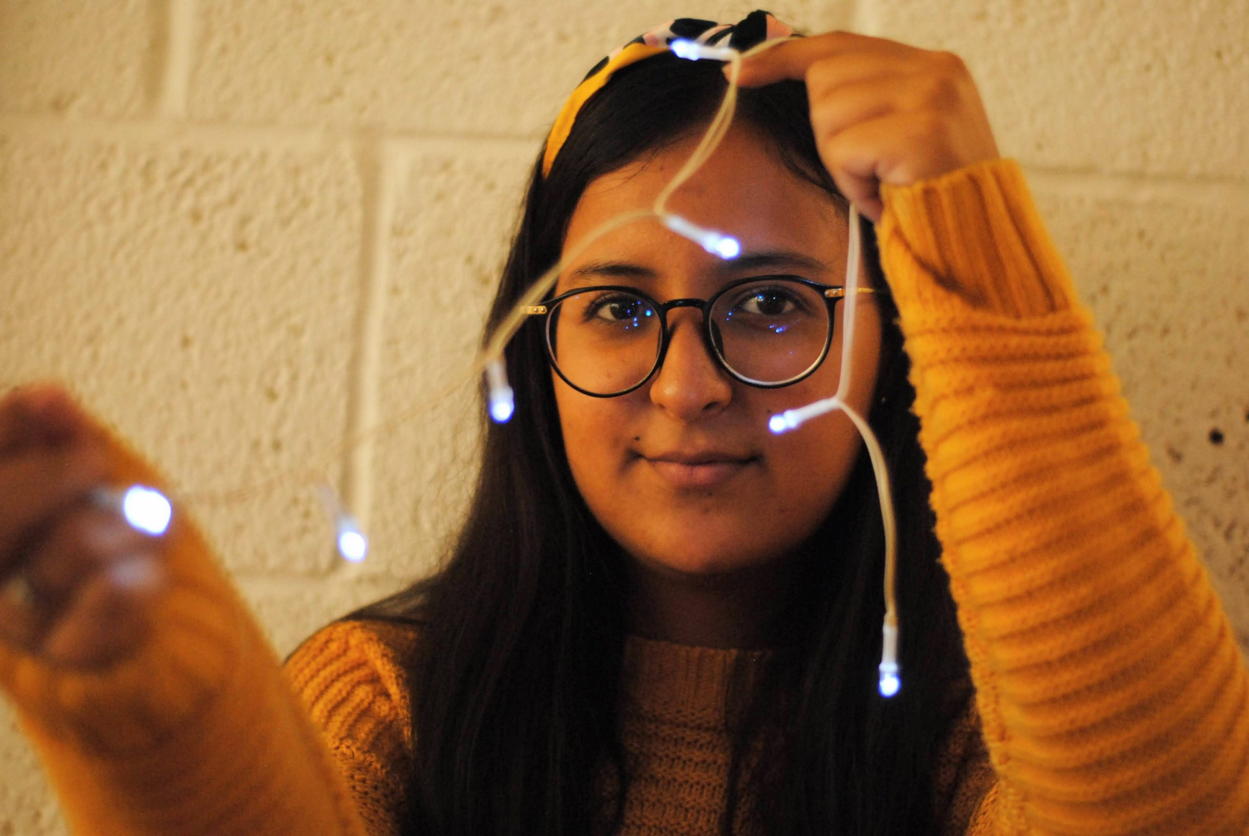 portrait image of girl wearing glasses and yellow jumper holding fairy lights