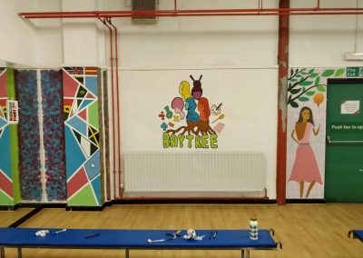 three separate murals painted on wall. far left is painted on protruding beam and has geometric shapes in different colours and flags painted in them. second mural in the middle says baytree at the bottom in green paint and merges into roots of a tree trunk, different female portraits coming off tree. mural on far right is of a woman in a long, pink dress under a tree holding a yellow balloon which also looks like a light bulb