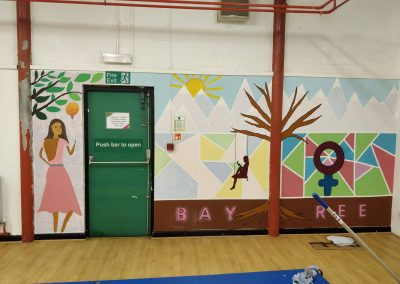 mural on gym wall. on left hand side is mural of woman in a long, pink dress under a tree, holding a yellow balloon that also looks like a light bulb. mural on right has brown strip at the bottom and says 'baytree'. a tree goes through the middle of the wall with girl on swing hanging off one branch. background has light blue, yellow and white geometric shapes with mountains coming through at the top of the wall. on the right the geometric shapes are green, pink and a darker blue.